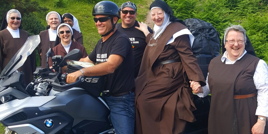 Group of nuns in surrounding a motorcyclist all laughing