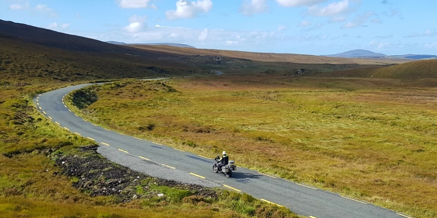 Grassy, hilly landscape with a narrow tar road with yellow broken lines running along the sides and a lone motorcyclist riding away. Blue sky with fluffy clouds.