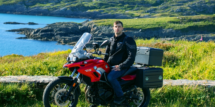 Man sitting on a red BMW motorbike on the side of the road with a rough landscape jutting into the ocean behind him.